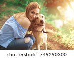 woman playing with her dogs at... | Shutterstock . vector #749290300