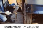 change a flat car tire on road... | Shutterstock . vector #749313040