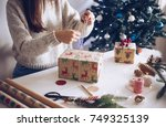 woman wrapping christmas gift | Shutterstock . vector #749325139