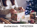 woman wrapping gifts for... | Shutterstock . vector #749325304
