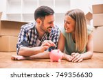 young couple is saving money... | Shutterstock . vector #749356630