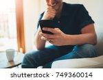 happy smiling man using his... | Shutterstock . vector #749360014