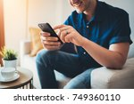 happy smiling young man using... | Shutterstock . vector #749360110
