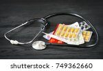 Small photo of aural instrument, graduate and pills on a wooden background