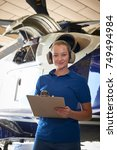 Small photo of Portrait Of Female Aero Engineer With Clipboard Carrying Out Check On Helicopter In Hangar