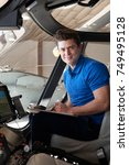 Small photo of Portrait Of Male Aero Engineer With Clipboard Working In Helicopter Cockpit