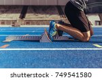 Small photo of Athlete on his mark ready to sprint on an all-weather running track. Runner using a starting block to start his run on race track.