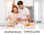 young couple together cooking ... | Shutterstock . vector #749551240