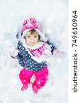 a child plays in the snow in... | Shutterstock . vector #749610964