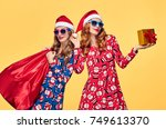 christmas. two young woman and... | Shutterstock . vector #749613370