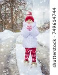 a child plays in the snow in... | Shutterstock . vector #749614744