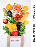 Small photo of Healthy food background. Healthy food in paper bag fish, vegetables and fruits on white. Shopping food concept. Top view