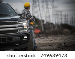 Caucasian Contractor Field Work Job. Worker and His Pickup Truck. Countryside Remote Location with High Voltage Poles in the Background. - stock photo