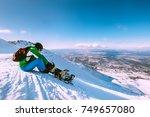 snowboarder fastens snowboard... | Shutterstock . vector #749657080