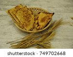 """Small photo of Algerian traditional dish """"kessra"""" with ears wheat and white background"""