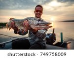 happy angler holds pike fish ... | Shutterstock . vector #749758009