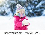 child playing with snow in... | Shutterstock . vector #749781250