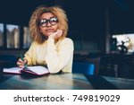 Stock photo thoughtful young woman in eyeglasses writing to do list of goals writing in diary in coffee shop 749819029