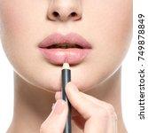 girl apply lipstick with... | Shutterstock . vector #749878849