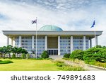 The main view of the National Assembly Proceeding Hall at Seoul in the Republic of Korea. The building of the South Korean national government. The flag of the South Korea on the sky background.