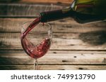 pouring red wine in a glass on... | Shutterstock . vector #749913790