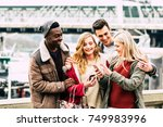 Stock photo group of multiracial friends using mobile smart phone in the city during best friends meeting 749983996