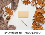 Small photo of Unsigned envelope and pen on white wooden table with autumn accessories. View from above.