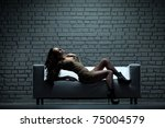Beautiful model in stylish dress laying on sofa - stock photo