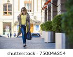 a young girl walks by the store | Shutterstock . vector #750046354