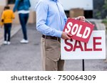 realtor hanging sold sign in... | Shutterstock . vector #750064309