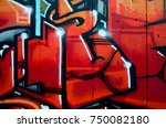 Small photo of A fragment of detailed graffiti of a drawing made with aerosol paints on a wall of concrete tiles. Background image of street art in warm red color tones