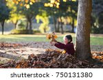 little girl playing with fallen ... | Shutterstock . vector #750131380