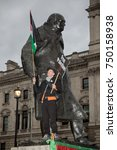 4th November 2017, London, United Kingdom:-Pro palestine protester standing on the statue of Winston Churchil in parliment square - stock photo