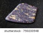 Small photo of macro shooting of natural mineral rock specimen - tumbled Alunite stone on dark granite background from Zaglik, Dashkasan region of Azerbaijan