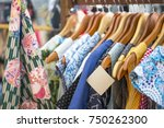Paper price tag hanging on colorful vintage dress