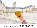 Holding a jar with famous dijon mustard on the main square background in Dijon city, France