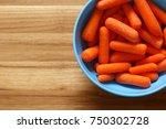 baby cut carrots in blue bowl... | Shutterstock . vector #750302728