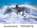 riding the waves. costa rica ... | Shutterstock . vector #750428578