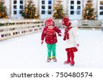 kids ice skating in winter park ... | Shutterstock . vector #750480574