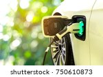 Stock photo ev car or electric car at charging station with the power cable supply plugged in on blurred nature 750610873