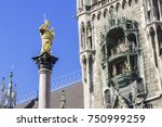 An image of the golden Maria statue in Munich with the city hall