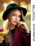 Small photo of Close up portrait of a Beautiful girl in a claret coat and black hat standing near colorful autumn leaves. Art work of romantic woman .Pretty tenderness model looking at camera.