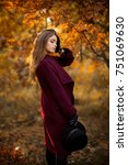 Small photo of Beautiful girl in claret coat and gloves standing near colorful autumn leaves. Art work of romantic woman .Pretty tenderness model in sun light on sunset looking down.