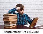 schoolboy reading electronic...   Shutterstock . vector #751217380