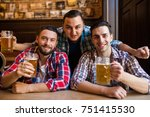 three young men are smiling and ... | Shutterstock . vector #751415530