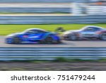 Small photo of Motion Blur race car racing on speed track, Super car race on the international race track.