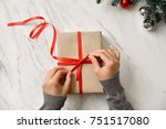 female hands wrapping a brown... | Shutterstock . vector #751517080