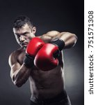 Small photo of Boxing concept. Boxer with an aggressive look in red boxing gloves before a fight against a black background