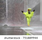 Small photo of man with yellow protective suit and splashes of water to decontaminate the surrounding environment