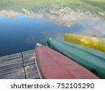 Small photo of A red canoe, a green canoe, and a yellow canoe upturned on a wood boat dock in a lake, with the reflection of a snow-capped mountain, in the Canadian Rockies, British Colombia, Canada. Room for text.